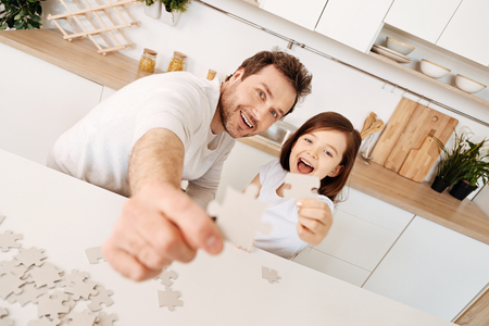 Father and daughter raising jigsaw puzzle pieces