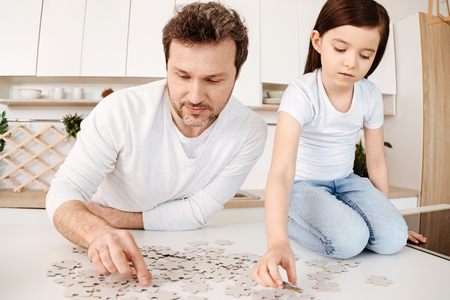 upbringing: Father and daughter doing a jigsaw puzzle in the kitchen