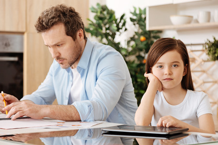 upbringing: Loving daughter sitting near her busy father