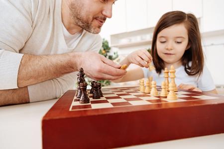 estereotipo: Padre ayudando a su hija a establecer un tablero de ajedrez Foto de archivo