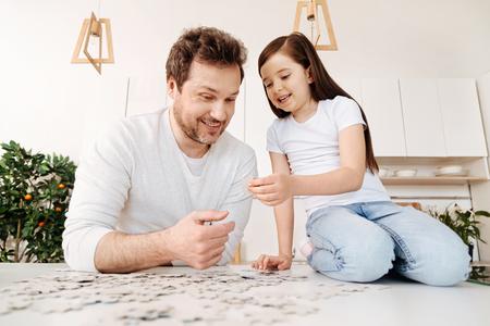 estereotipo: Pequeña hija mostrando a su padre una pieza de rompecabezas