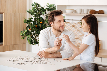 Father and daughter uniting two jigsaw puzzle pieces