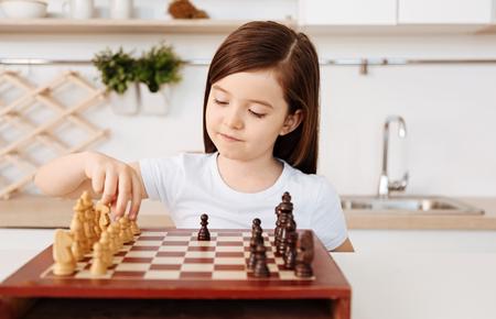 Smart little girl playing chess alone