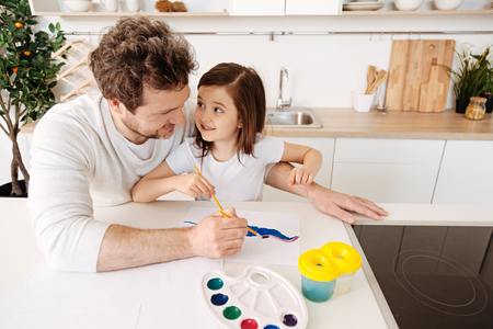 upbringing: Happy father painting together with his daughter Stock Photo