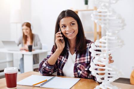 genomics: Committed excited woman calling someone while studying