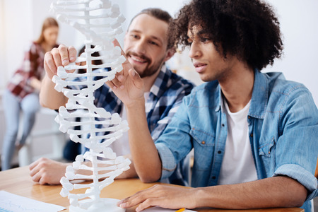 Excited young scientists discovering the structure of human genome