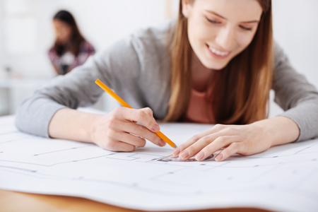 Mindful persistent young woman working on a draft