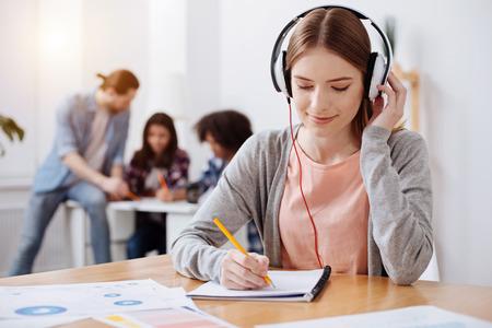 Aufmerksamer produktiver junger Student, der eine Abschrift macht Standard-Bild - 79623424