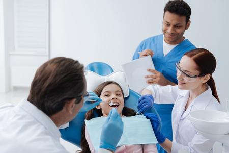 Experienced stomatologist doing teeth checkup Stock Photo