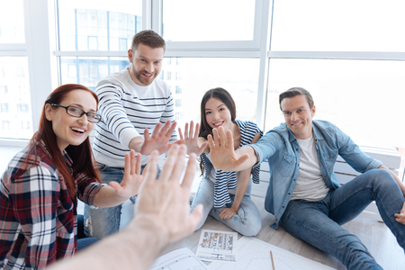 Happy delighted people giving high five Stock Photo