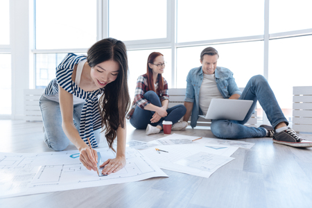 Joyful Asian woman working on a blueprint