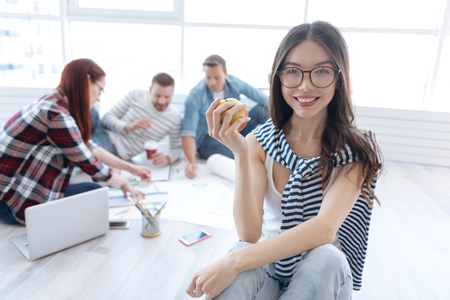 Delighted positive woman having an apple in her hands