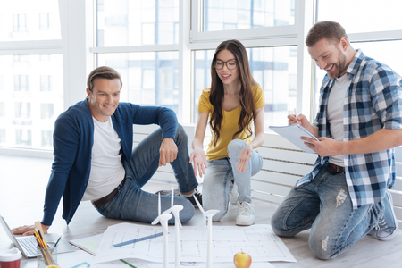 Positive delighted man sitting near his colleague Stock Photo