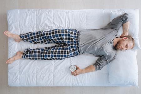 drowsy: Handsome brutal man enjoying last minutes of sleep Stock Photo