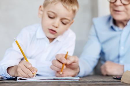 Persistent kid and his grandpa preparing for school together Фото со стока