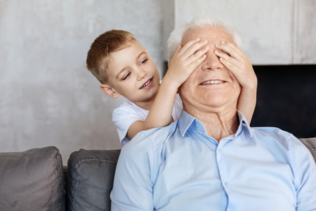 baby boomer: Sweet sincere boy playing with his grandpa
