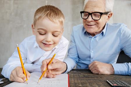 열심히 좋은 남자가 손자 손을 가르치다.