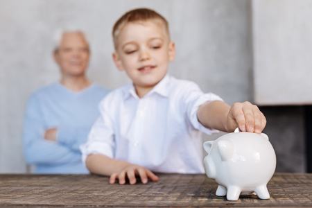 Inspired young kid sparing money for a dream Фото со стока