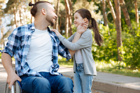 Delighted man touching ear of his daughter