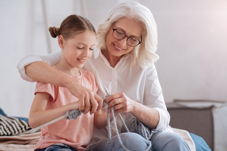 Delighted cute girl learning to knit Stock Photo