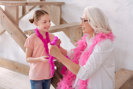 boas: Nice delighted grandmother and granddaughter wearing feather boas