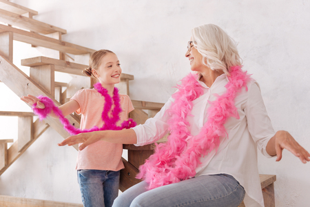 Delighted positive grandmother and granddaughter having fun together Фото со стока