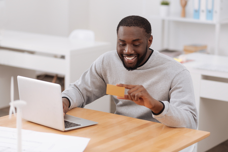 Positive happy man holding a credit card