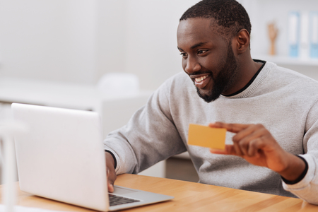 Cheerful pleasant man making an online payment