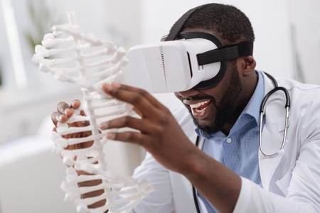 genomics: Happy delighted man studying the DNA model