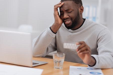 Trauriger, launischer Mann mit Kopfschmerzen Standard-Bild - 80550544