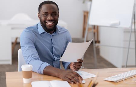 Joyful positive man sitting on the table