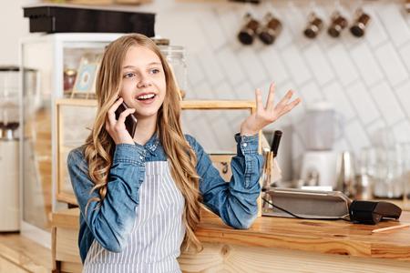 Pretty teenage girl talking on the phone at work