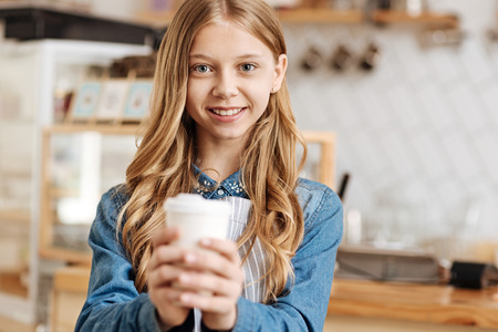 Joyful teenage barista warming hands around a coffee cup Stock Photo