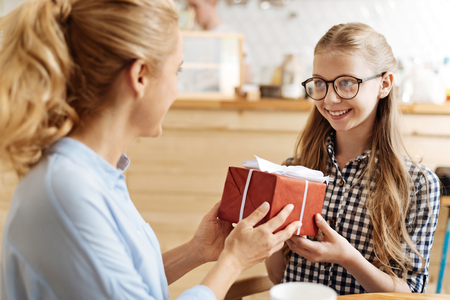 Charming teenage girl being happy to get a present Stock Photo