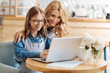 printout: Caring mother helping her daughter with home assignment