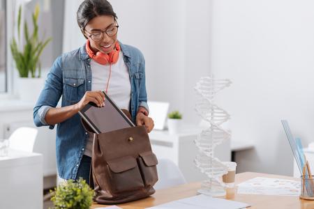 Mooie blikvrouw die de tablet in haar tas plaatste Stockfoto