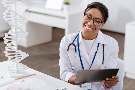 genomics: Cheerful experienced doctor using a tablet