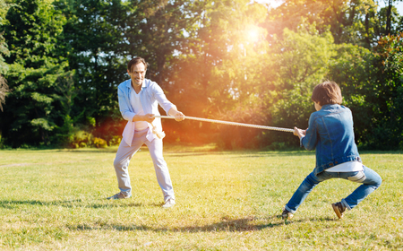 Adorable kid and his dad finding out who being stronger Standard-Bild