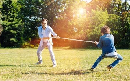 Schattige jongen en zijn vader ontdekken wie sterker is Stockfoto