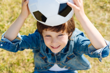 upbringing: Attractive smart kid holding the ball up