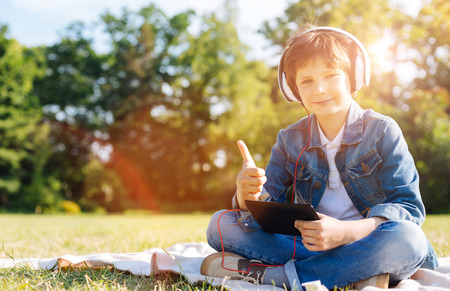 Attractive positive child using his tablet at the picnic Stock Photo
