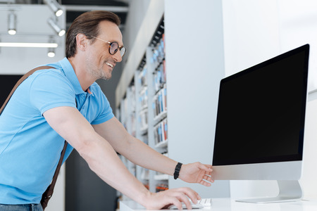 shopper: Radiant male shopper looking at computer screen Stock Photo