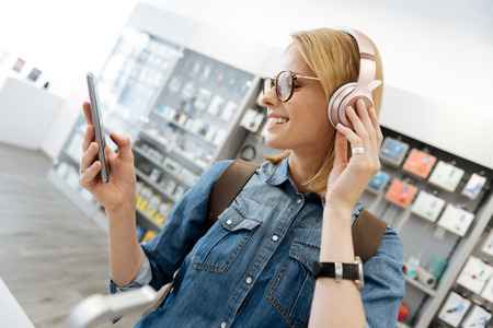 Smiling blonde lady using mockup headphones at shop