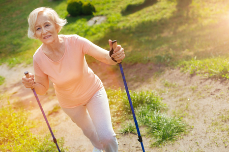 Happy delighted woman using walking poles