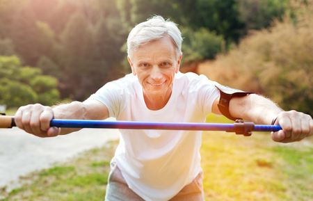 Cheerful active man exercising with a walking pole Stock Photo