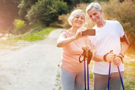 Positive aged woman holding a smartphone