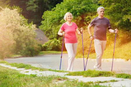 Positive sporty couple walking along the road