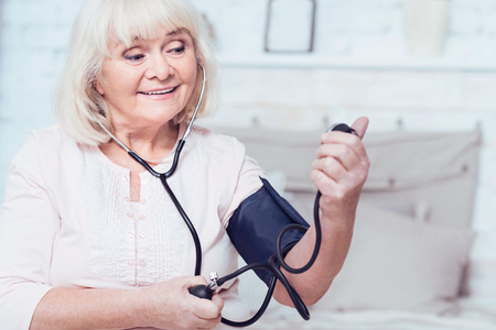 Optimistic aging woman checking blood pressure at home Stock Photo