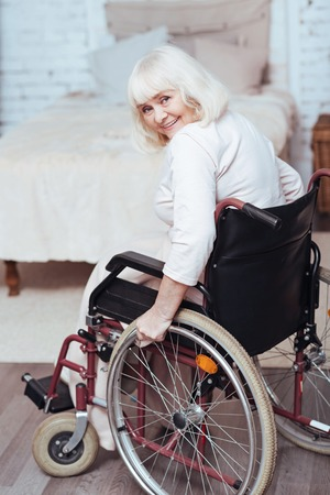 Optimistic aged disabled lady smiling at home Stock Photo