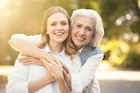 Positive woman enjoying walk with elderly parent on the street